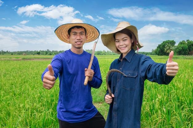 O agricultor asiático masculino e feminino, de uniforme azul, usa um chapéu, segura o dispositivo e segura o polegar com um sorriso no campo verde do céu. com bons resultados de produção Foto Premium