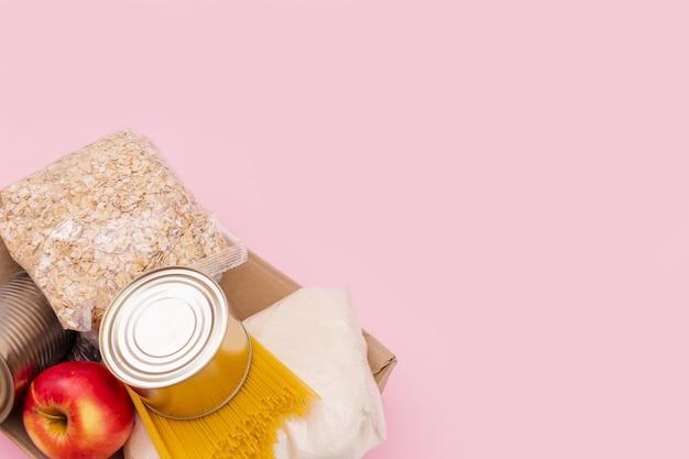 O alimento para o período de isolamento da quarentena liso coloca no espaço amarelo com espaço da cópia. ovos, macarrão, feijão, papel higiênico, maçã e algumas seleções. Foto Premium