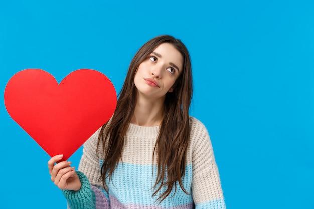O amor é para idiotas. universitária atraente, impressionada e despreocupada, descuidada, revirar os olhos e desviar o olhar desinteressada, segurando um grande coração vermelho, dong care no dia dos namorados, em pé azul Foto Premium