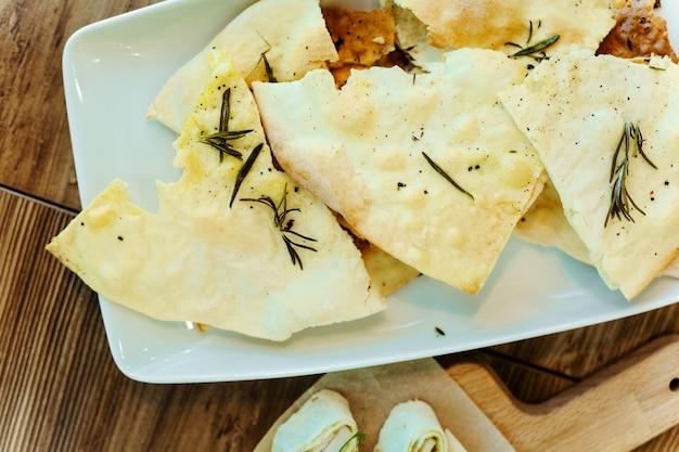 O aperitivo do pão do pão árabe cozeu com azeite e alecrins em uma placa branca na tabela de madeira. Foto Premium