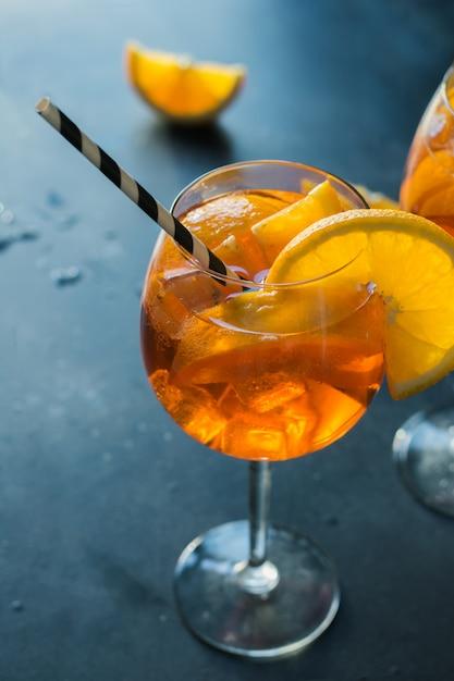 O aperol italiano clássico spritz o cocktail na obscuridade. Foto Premium