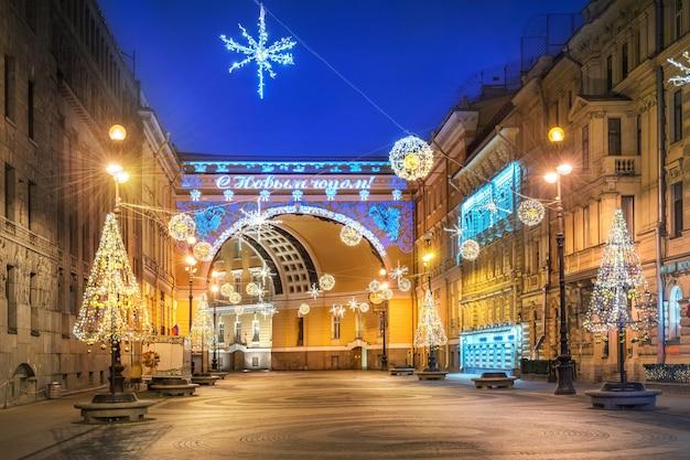 O arco do triunfo na praça do palácio em são petersburgo e as decorações de ano novo à luz de uma noite azul de inverno. legenda: feliz ano novo! Foto Premium