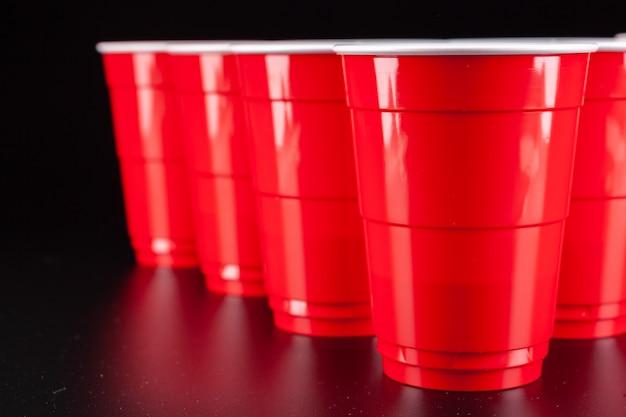 O arranjo de copos de plástico vermelhos para o jogo de pong de cerveja Foto Premium