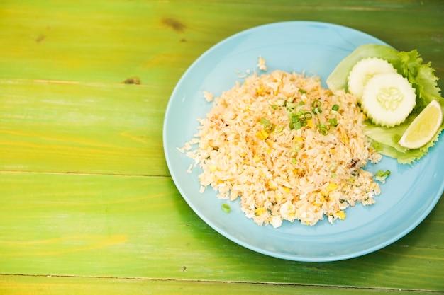 O arroz fritado com carne de caranguejo nos pratos pôs sobre a tabela verde. Foto Premium