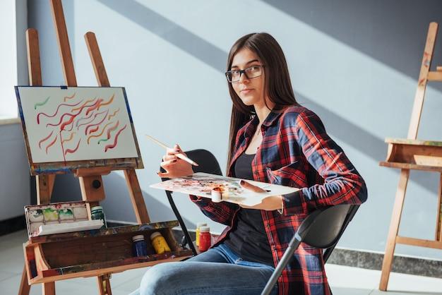 O artista pretty pretty girl pinta sobre tela no cavalete. Foto Premium
