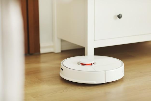 O aspirador de pó robô executa a limpeza automática do apartamento em um determinado momento. aspirador de pó robô branco. limpeza doméstica. lar inteligente. foco seletivo Foto Premium
