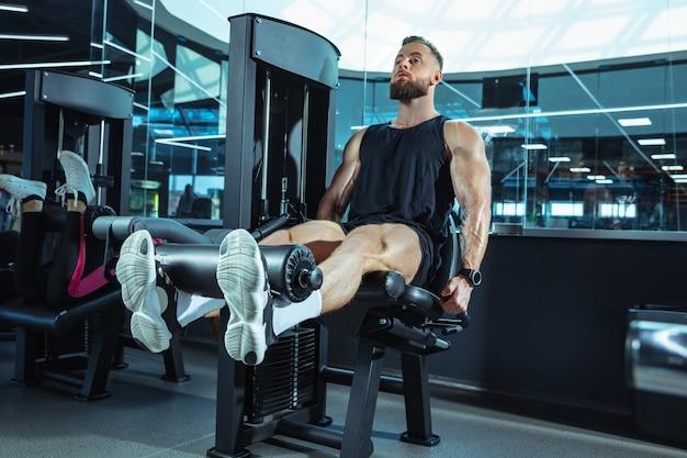 O atleta do sexo masculino treinando duro no ginásio. fitness e conceito de vida saudável. Foto gratuita
