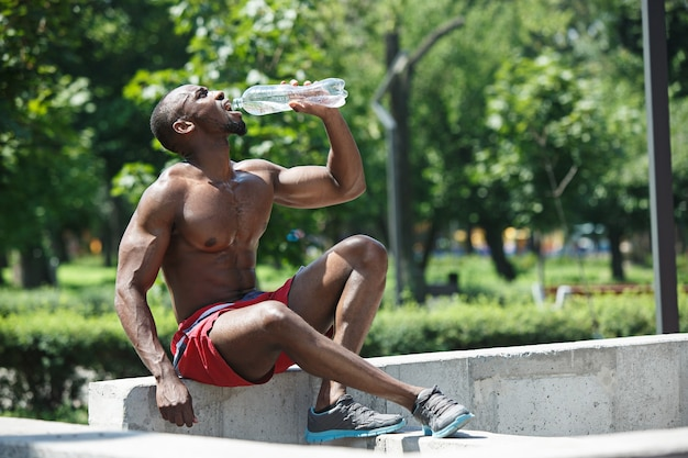 O atleta em forma descansando e bebendo água após os exercícios no estádio. homem afro-americano ao ar livre na cidade. fitness, saúde, conceito de estilo de vida Foto gratuita