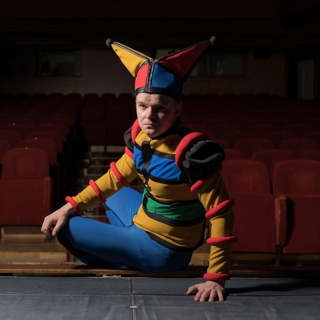 O ator vestiu a fantasia de bobo da corte no interior do antigo teatro. Foto Premium