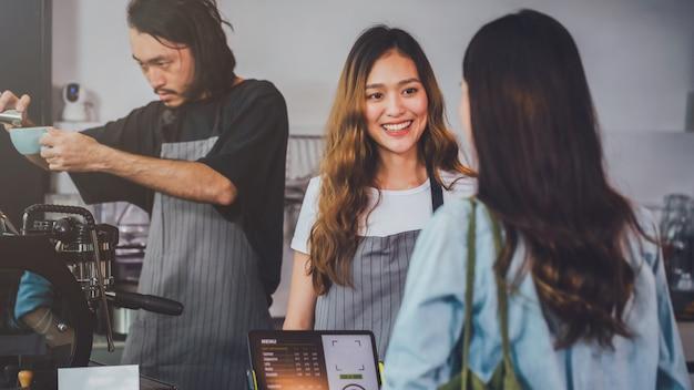 O avental asiático bonito novo do desgaste do barista da mulher que guarda o copo de café quente serviu ao cliente no contador da barra na cafetaria com cara do sorriso. Foto Premium