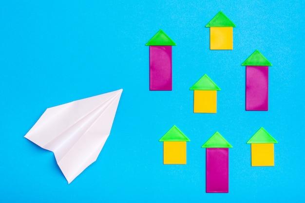 O avião de papel branco sobrevoa figuras coloridas de casas em um cartão azul. vista do topo. conceito de perigo de acidente de avião Foto Premium