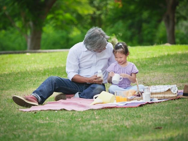 O avô passa o tempo no feriado com os netos no parque natural. Foto Premium