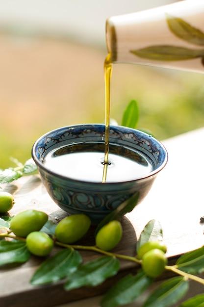 O azeite no copo. ramo de uma oliveira com azeitonas frescas. azeitonas verdes. no jardim. em uma placa de madeira. um jarro de óleo. clássicos italianos. azeitonas da itália. comida da itália Foto Premium