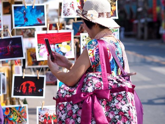 O backpacker asiático das mulheres que procura está vendo fotos das atrações turísticas no festival do turismo de tailândia. Foto Premium