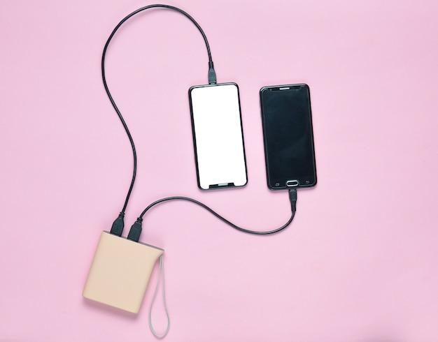 O banco de potência cobra dois smartphones em uma superfície pastel. aparelhos modernos. vista do topo. minimalismo Foto Premium