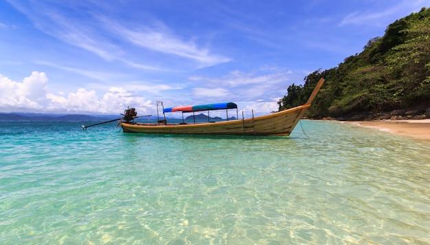 O barco do pescador flutua no mar azul com a praia branca da areia e o céu azul bonito. ilha kangkao. Foto Premium