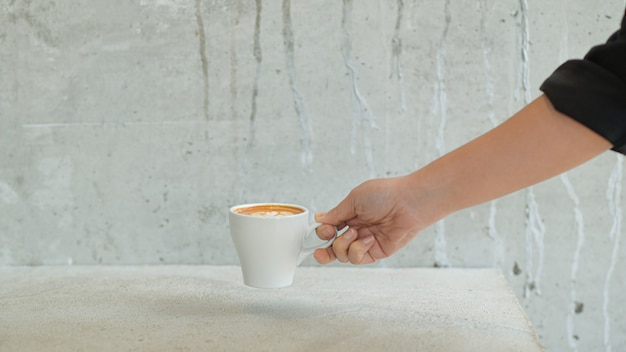 O barista feminino coloca uma xícara de café na mesa para servir o cliente. Foto Premium