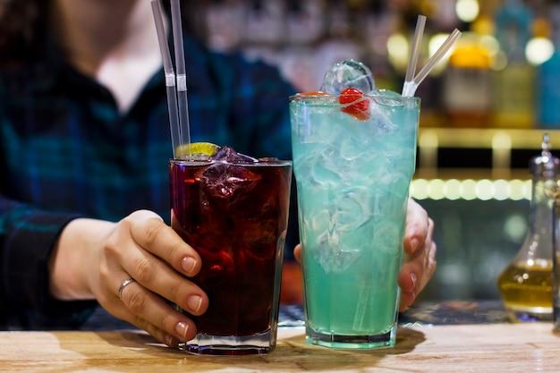 O barman menina segurando duas bebidas no bar Foto Premium