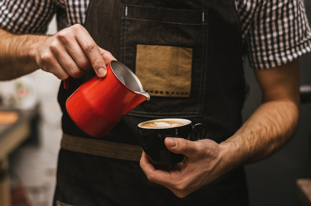 O barman no local de trabalho. barman masculino faz cappuccino. Foto Premium