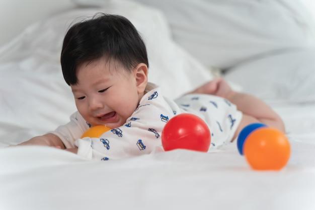 O bebê asiático está rindo e jogando bola de brinquedo na cama branca com sentimento feliz e alegre e o bebê que rasteja na cama. Foto Premium