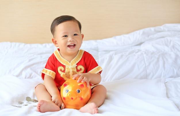 O bebê asiático pequeno feliz no chinês tradicional veste-se com um mealheiro na cama. Foto Premium