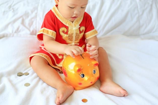 O bebê asiático pequeno no chinês tradicional veste a colocação de algumas moedas em um banco piggy na cama. Foto Premium