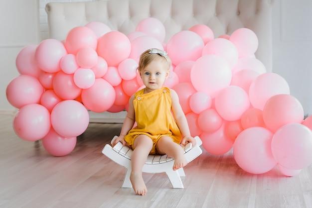 O bebê considerável com cabelo dourado vestiu o romper amarelo que senta-se no banco branco pequeno. momentos felizes, balões cor de rosa. garoto bonito e bonito, primeiro aniversário. Foto Premium