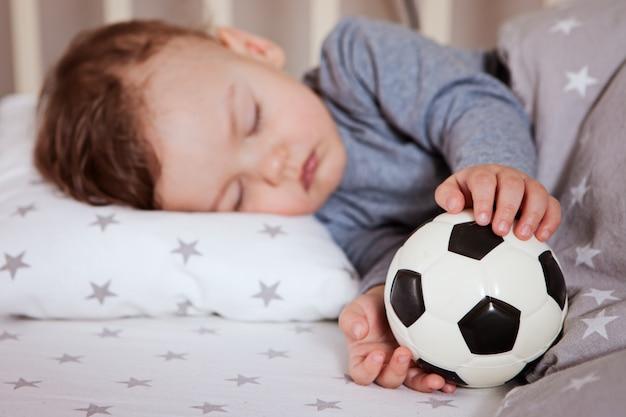O bebê está dormindo em um berço com uma bola de futebol na mão. Foto Premium