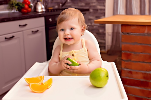 O bebê feliz de 10 a 12 meses come frutas: laranja, maçã. retrato de uma menina feliz em uma cadeira na cozinha Foto Premium