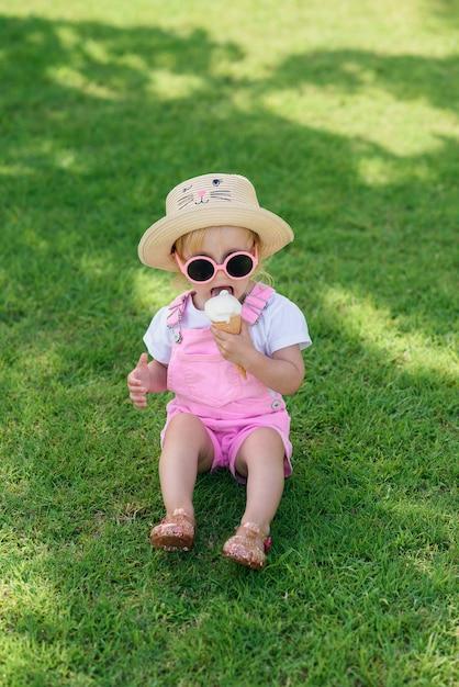 O bebê feliz vestiu a roupa cor-de-rosa do verão, chapéu amarelo e óculos de sol cor-de-rosa senta-se em um gramado verde e come-se o gelado branco em um jardim ensolarado. Foto Premium