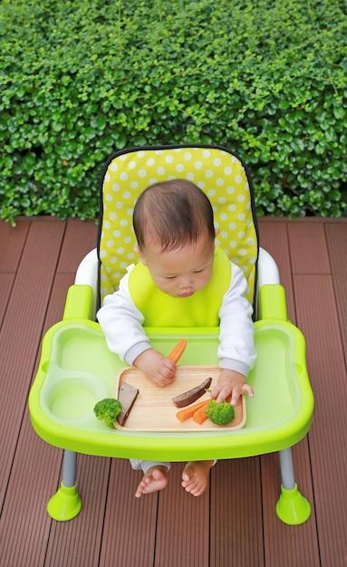 O bebê infantil asiático que come pelo bebê conduziu o desmame (blw). conceito de alimentos de dedo. Foto Premium