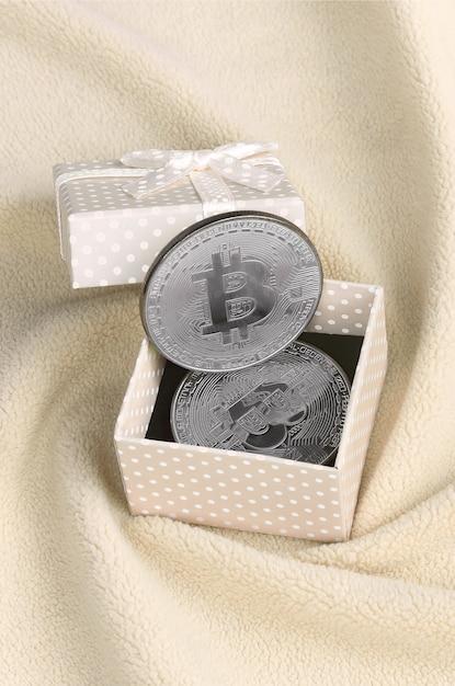 O bitcoin de prata encontra-se em uma pequena caixa de presente laranja com um pequeno arco Foto Premium