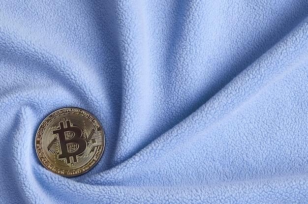 O bitcoin dourado encontra-se em um cobertor Foto Premium