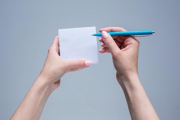 O bloco de notas e a caneta em mãos femininas em fundo cinza Foto gratuita