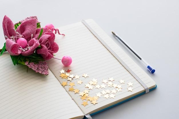 O bloco de notas em branco com o ramalhete de flores da mola e vislumbra estrelas. Foto Premium
