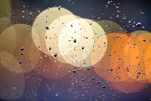O bokeh colorido abstrato com círculos e água amarelos deixa cair na superfície do vidro na parte dianteira. luzes da cidade turva. Foto Premium