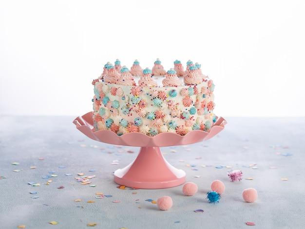 O bolo de aniversário colorido com polvilha sobre o branco. Foto Premium