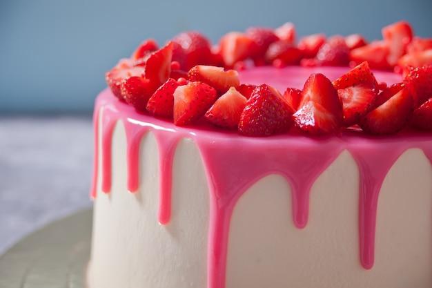 O bolo delicioso do aniversário com esmalte cor-de-rosa decorou morangos frescas. Foto Premium