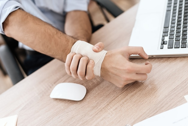 O braço de um homem está doendo. dói ele, ele sofre. Foto Premium