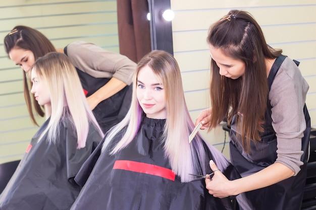O cabeleireiro corta o cabelo de uma menina com uma tesoura. garota em um salão de beleza, cuidados com os cabelos Foto Premium