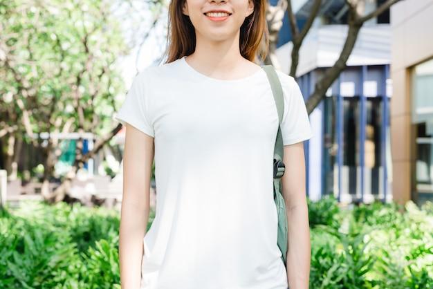 O cabelo marrom longo da menina asiática do moderno no t-shirt vazio branco está estando no meio da rua. um fem Foto gratuita