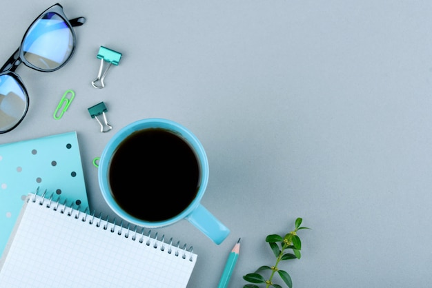O caderno azul com corrige em um cinza. telefone, copos e uma xícara de café. Foto Premium