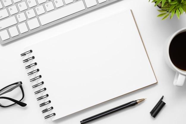 O caderno vazio está sobre a tabela branca moderna da mesa de escritório com fontes. vista superior com espaço da cópia, configuração lisa. Foto Premium