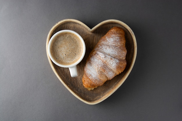 O café com o croissant no coração de madeira deu forma à caixa. Foto Premium