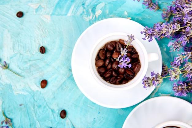O café da grão em copos e a alfazema florescem no fundo azul de cima de. Foto Premium