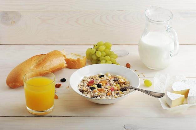 O café da manhã continental é composto por cereais, uvas, suco de laranja, leite, pão, baguete, queijo Foto Premium