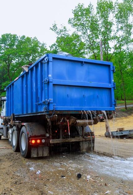 O caixote do lixo perto de um recipiente de metal sem lixo, sem tampa, está cheio de resíduos de detritos de construção que estão no prédio em construção Foto Premium