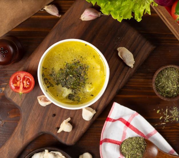 O caldo de galinha com sopa das ervas na bacia descartável do copo serviu com vegetais verdes. Foto gratuita