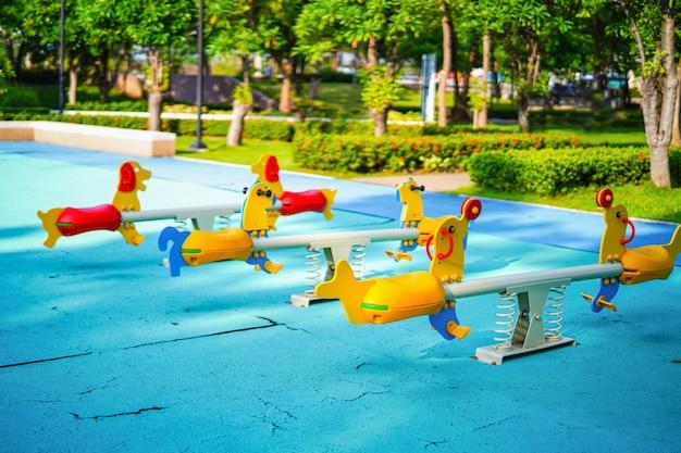 O campo de jogos para crianças da criança caçoa tendo o divertimento com a balancê colorida em atividades da jarda no parque público. Foto Premium