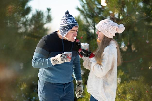 O cara com a garota anda e beija na floresta de inverno com uma caneca de bebida quente Foto Premium